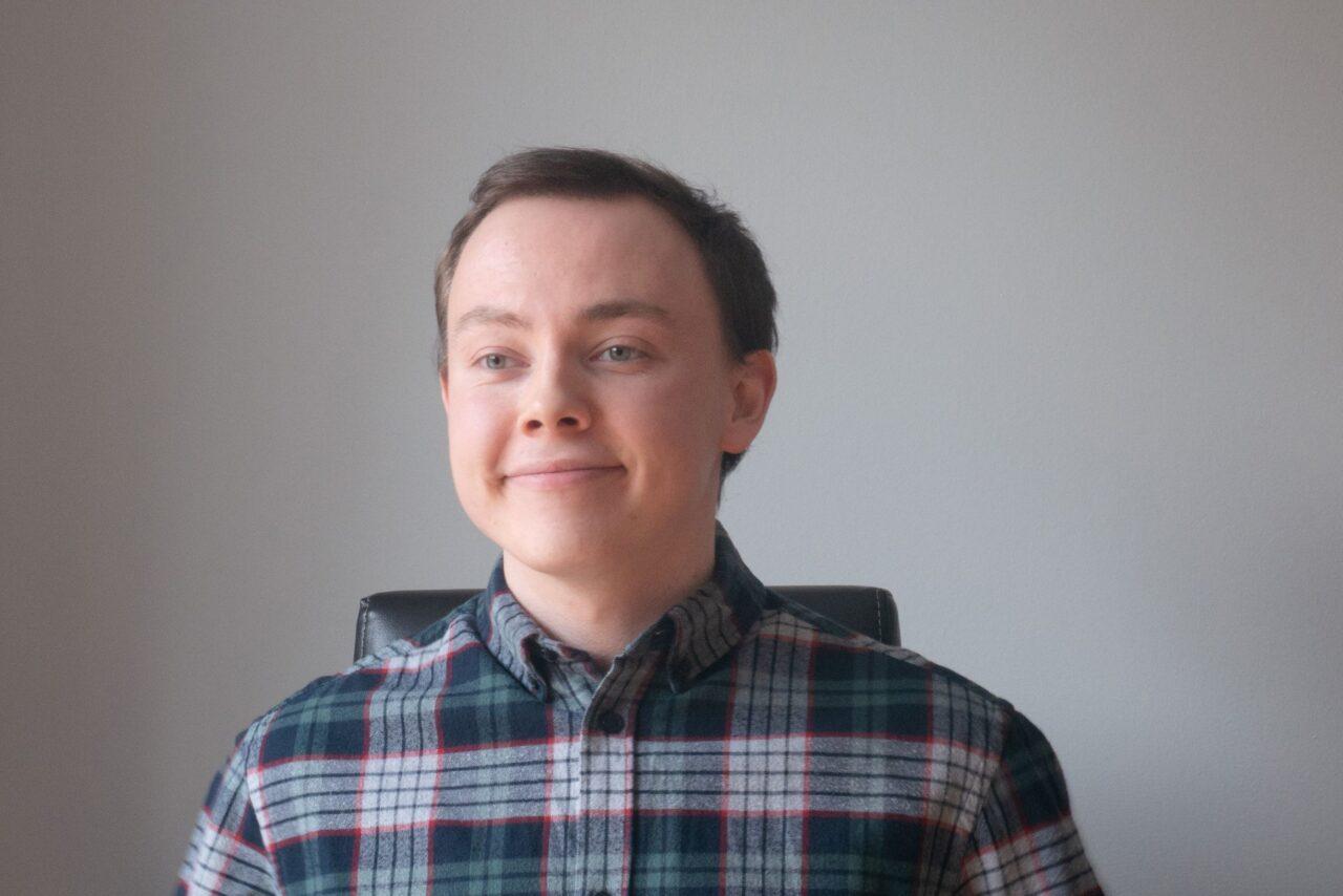 Young man, looking at his laptop, wearing a shirt